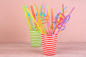 Straws in cups on pink background — Stock Photo