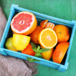 Fresh citrus fruits with green leaves in wooden box on color wooden background — Stock Photo #47852473