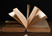 Old book on table on black background — Stock Photo
