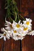 Beautiful bouquet of daisies on wooden background — Stock Photo