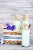 Bottles of milk and cornflowers in wicker basket on wooden background — Stock Photo