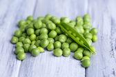 Fresh green peas on wooden background — Stock Photo