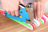 Fastening fabric and board using construction stapler — Stock Photo