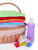 Bright clothes in laundry basket, pins and bottle with shampoo for washing, isolated on white — Stockfoto