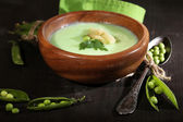 Tasty peas soup on wooden table with dark light — Stock Photo