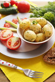 Young boiled potatoes in pan on wooden table — Stock Photo