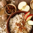 Tasty oatmeal with nuts and apples on wooden table — Stock Photo #47906827