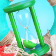 Hourglass in sand on blue sky background — Stock Photo #47908029