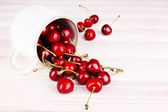 Ripe sweet cherries in cup on wooden table — Stock fotografie