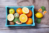 Fresh exotic fruits with green leaves in wooden box on color wooden background — Stock Photo
