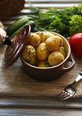 Young boiled potatoes in pan on wooden table — Stock fotografie
