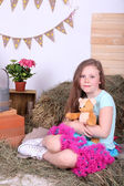 Beautiful small girl in petty skirt holding teddy bear on country style background — Zdjęcie stockowe