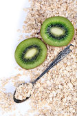Kiwi fruit with oatmeal and vintage spoon isolated on white — Stock fotografie