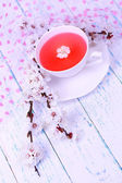 Fragrant tea with flowering branches on wooden table close-up — Stock Photo