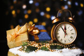 Alarm clock with snow and presents on table on bright background — Stock Photo