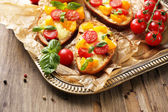 Tasty bruschetta with tomatoes, on old wooden table — Stock fotografie