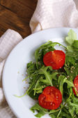 Green salad made with  arugula, tomatoes and sesame  on plate, on wooden background — Stock fotografie