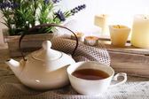 Composition with tea in cup and teapot and candles on table, on light background — Stock Photo
