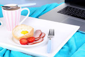 Composition with laptop and tasty breakfast on wooden tray, close-up, on bright background — Stock fotografie