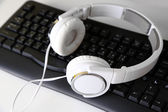 Headphone and keyboard close-up on white desk background — Stock Photo