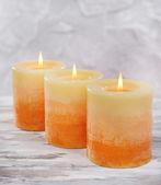 Piękne świece na stole na szarym tle — Zdjęcie stockowe