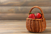 Red ripe strawberries in wicker basket on wooden background — Zdjęcie stockowe