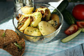 Young boiled potatoes in bowl on wooden table, close up — Stock fotografie