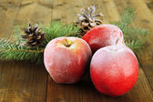 Red frosted apples with fir branch and bumps on wooden background — Stock Photo