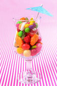 Different colorful fruit candy in glass on pink background — Stock fotografie