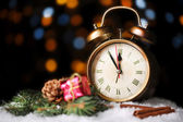Alarm clock with snow and Christmas decoration on table on bright background — Stock Photo