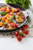 Tasty bruschetta with tomatoes in pan, on table — Stock fotografie