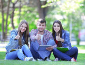 Happy students sitting in park — ストック写真