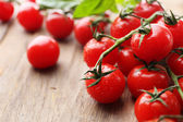 Fresh cherry tomatoes on old wooden table — Stock Photo