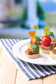 Tasty canapes with salami,tomato, pepper  and basil leaves, on plate, on wooden table, on bright background — Stock Photo