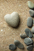 Grey stone in shape of heart, on sand background — Stock Photo