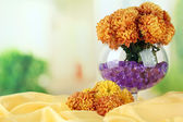 Beautiful flowers in vase with hydrogel on table on bright background — Stock Photo