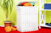 Full laundry basket  on wooden floor on  home interior background — Stockfoto