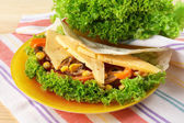Veggie wrap filled with cheese and fresh vegetables on table, close up — Stock Photo