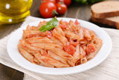 Pasta with tomato sauce on plate on table close-up — Stock fotografie