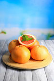 Ripe grapefruits on wooden table, on bright background — Stock Photo