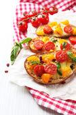 Tasty bruschetta with tomatoes, on table — Stock fotografie