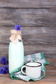 Bottle and cup of milk with cornflowers on wooden background — Stock fotografie