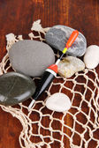 Fishing float with stones on wooden table close-up — Stock Photo