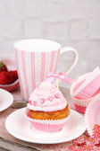 Tasty cup cake with cream on wooden table — Stock fotografie