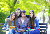 Happy students sitting in park — Photo