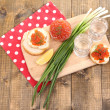 Red caviar in bowl and vodka on wooden board , on napkin on wooden background — Stock Photo #47914967