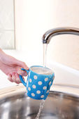 Hand holding  cup of water poured from  kitchen faucet — Stok fotoğraf