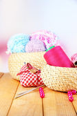 Handicraft supplies in basket on wooden table on bright background — Stock Photo