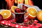 Fragrant mulled wine in glass on napkin on fire background — Stock Photo