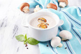 Mushroom soup in white pot, on napkin,  on wooden background — Stock Photo